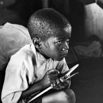 Earnest boy squats on haunches and strains to follow lesson in heat of packed classroom, 1960-1966 © The Ernest Cole Family Trust Courtesy of the Hasselblad Foundation, Gothenburg, Sweden